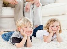 Aanbiddelijke familie die op TV let Royalty-vrije Stock Foto's