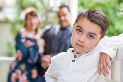 Aanbiddelijke Gemengde Rasjongen die zich voor Ouders bevinden stock afbeelding