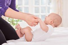 Aanbiddelijke het glimlachen babypraktijk op bed met moeder Royalty-vrije Stock Foto