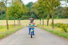 Aanbiddelijke jong geitjejongen die van 4 jaar op fiets berijdt Royalty-vrije Stock Afbeeldingen