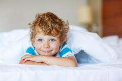 Aanbiddelijke jong geitjejongen na het slapen in zijn wit bed royalty-vrije stock afbeelding