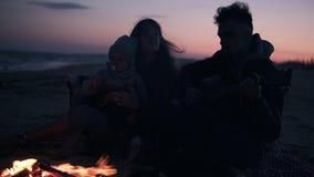Aanbiddelijke, jonge familie samen met hun dochter op het strand met een brand en een gitaar, het concept familiewaarden stock video