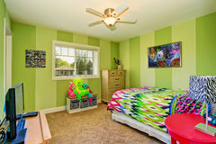 Aanbiddelijke jonge geitjesruimte in groene kleur met helder kleurrijk beddegoed stock afbeeldingen
