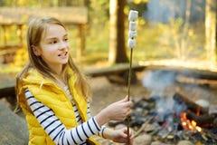 Aanbiddelijke jonge meisjes roosterende heemst op stok bij vuur Kind die pret hebben bij kampbrand Het kamperen met kinderen in d stock foto