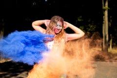 Aanbiddelijke jonge vrouw die pret met exploderende droge Holi-verf hebben Royalty-vrije Stock Foto's