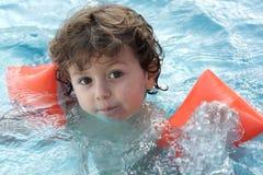 Aanbiddelijke jongen die leert te zwemmen stock foto's