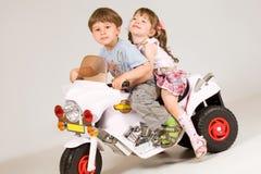 Aanbiddelijke jongen en meisjezitting op stuk speelgoed fiets stock foto's