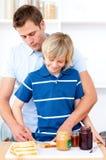 Aanbiddelijke jongen en zijn vader die ontbijt voorbereiden Royalty-vrije Stock Fotografie