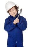 Aanbiddelijke jongen geklede arbeider in een hamer en een helm Royalty-vrije Stock Afbeeldingen