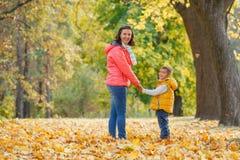 Aanbiddelijke jongen met zijn moeder in de herfstpark royalty-vrije stock foto