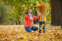 Aanbiddelijke jongen met zijn moeder in de herfstpark stock foto