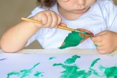 Aanbiddelijke kind het schilderen dalingsbladeren bij lijst stock afbeeldingen