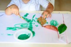 Aanbiddelijke kind het schilderen dalingsbladeren bij lijst royalty-vrije stock afbeeldingen