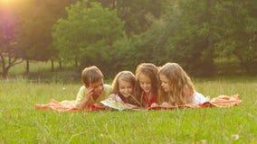 Aanbiddelijke kinderen die een boek op een aardige middag van de gazon samen zomer lezen stock footage