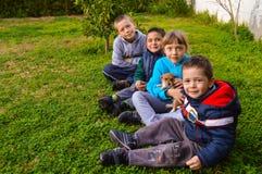 Aanbiddelijke kinderen die op het groene gazon met een kleine hond zitten Stock Afbeelding