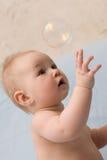 Aanbiddelijke kindzitting en het vangen van zeepbel Stock Fotografie