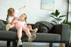 aanbiddelijke kleine kinderen die pret op bank hebben royalty-vrije stock afbeelding