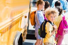 aanbiddelijke krullende schooljongen met zijn klasgenoten status stock foto