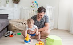 Aanbiddelijke 10 maanden oud babyjongen het spelen met vader op vloer bij slaapkamer Stock Afbeeldingen