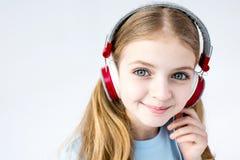 Aanbiddelijke meisje het luisteren muziek met hoofdtelefoons in studio royalty-vrije stock afbeelding