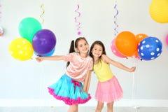 Aanbiddelijke meisjes bij verjaardagspartij binnen stock fotografie
