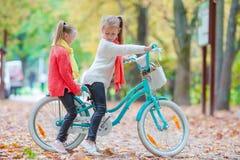 Aanbiddelijke meisjes die een fiets berijden bij mooi Stock Foto's