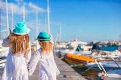 Aanbiddelijke meisjes die in een haven op de zomerdag lopen Stock Foto's