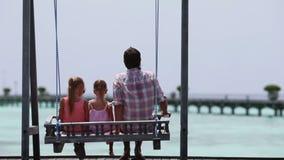 Aanbiddelijke meisjes en jonge vader op schommeling stock footage