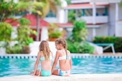 Aanbiddelijke meisjes in openlucht zwembad op vakantie Royalty-vrije Stock Foto's