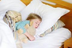 Aanbiddelijke meisjeslaap in het bed met haar stuk speelgoed Vermoeid kind die een dutje nemen onder witte deken Stock Afbeeldingen