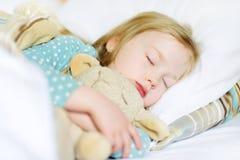 Aanbiddelijke meisjeslaap in het bed met haar stuk speelgoed Vermoeid kind die een dutje nemen onder witte deken Royalty-vrije Stock Fotografie