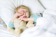 Aanbiddelijke meisjeslaap in het bed met haar stuk speelgoed Vermoeid kind die een dutje nemen onder witte deken Royalty-vrije Stock Foto's