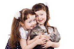 Aanbiddelijke meisjestweelingen met een kat Stock Foto