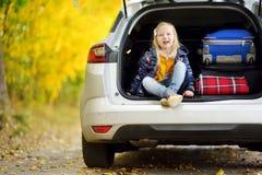 Aanbiddelijke meisjeszitting Ain een autoboomstam klaar om op vakanties met haar ouders te gaan Kind die vooruit voor een een weg Royalty-vrije Stock Foto's