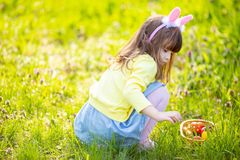 Aanbiddelijke meisjezitting bij het groene gras spelen in de tuin op paaseijacht royalty-vrije stock foto