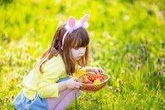 Aanbiddelijke meisjezitting bij het groene gras spelen in de tuin op paaseijacht royalty-vrije stock fotografie