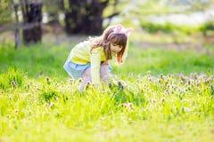 Aanbiddelijke meisjezitting bij het groene gras spelen in de tuin op paaseijacht royalty-vrije stock foto's