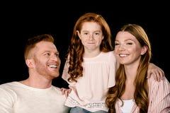 Aanbiddelijke ouders met weinig en dochter die geïsoleerd op zwarte glimlachen omhelzen royalty-vrije stock foto's