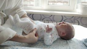 Aanbiddelijke pasgeboren baby die terwijl zijn moeder die hem kleden schreeuwen stock videobeelden