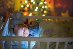 Aanbiddelijke pasgeboren babyjongen, die in voederbak bij nacht slapen royalty-vrije stock afbeeldingen