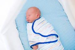 Aanbiddelijke pasgeboren die babyslaap in wit bed wordt ingewikkeld Royalty-vrije Stock Foto's
