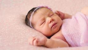 Aanbiddelijke pasgeboren weinig baby in roze deken ligt op bed stock video