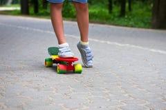 Aanbiddelijke peuterjongen die pret met kleurrijk skateboard in openlucht in het park hebben Stock Afbeeldingen