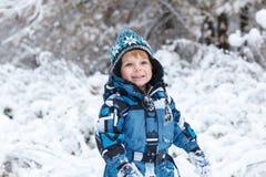 Aanbiddelijke peuterjongen die pret met sneeuw op de winterdag hebben stock afbeelding