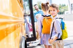 aanbiddelijke schooljongen die schoolbus met klasgenoten ingaan terwijl leraar status stock afbeelding