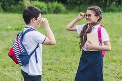 aanbiddelijke schoolkinderen die met rugzakken elkaar bekijken stock fotografie