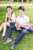 aanbiddelijke schoolkinderen die op gras zitten royalty-vrije stock afbeeldingen