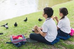 aanbiddelijke schoolkinderen die op gras zitten stock afbeeldingen