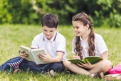 aanbiddelijke schoolkinderen die thuiswerk doen samen terwijl het zitten op gras stock fotografie