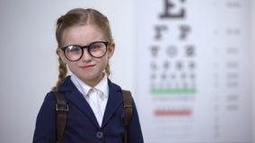 Aanbiddelijke schoolmeisje het aanpassen glazen, de preventie van de oogziekte, diagnostiek stock videobeelden